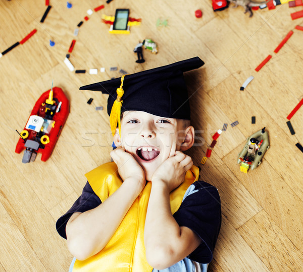 little cute preschooler boy among toys lego at home in graduate hat, educational people concept Stock photo © iordani