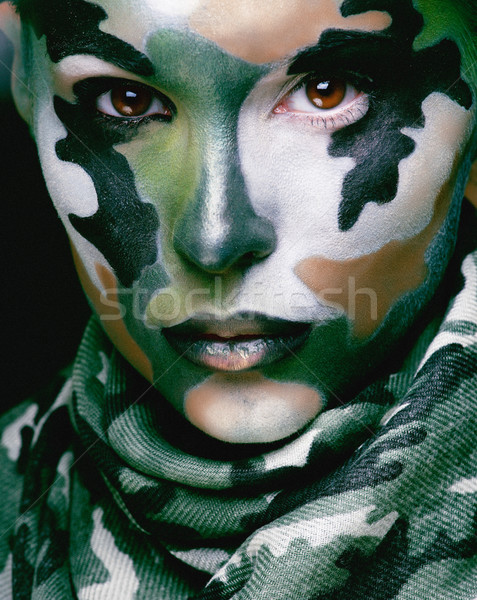 Beautiful young fashion woman with military style clothing and face paint make-up, khaki colors Stock photo © iordani