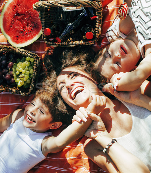 cute happy family on picnic laying on green grass mother and kids, warm summer vacations close up, b Stock photo © iordani