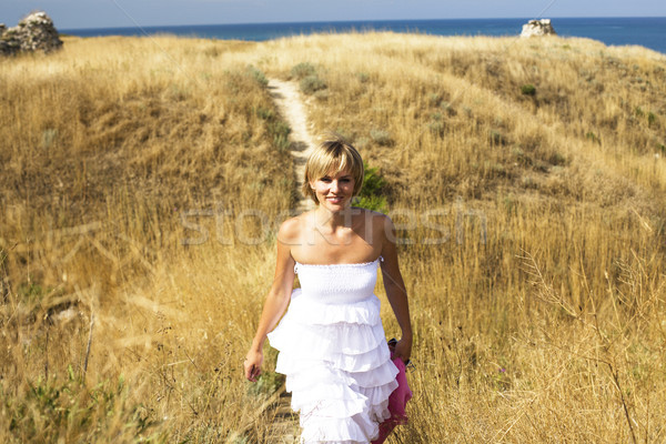 portrait of beautiful blond woman in white dress standing on wind with scarf near sea Stock photo © iordani