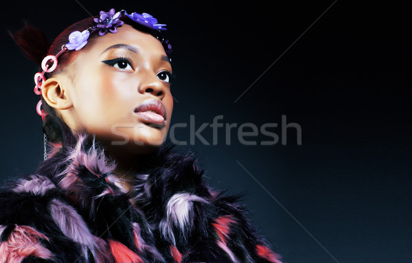 young pretty african american woman in spotted fur coat and flowers jewelry on head smiling sweet et Stock photo © iordani