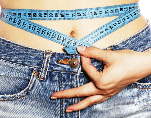 Stock photo: girls stomach measuring with tape twice isolated close up