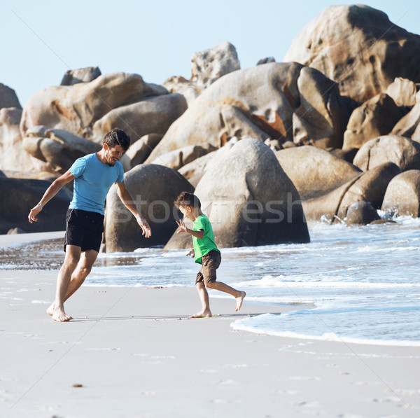 happy family on beach playing, father with son walking sea coast Stock photo © iordani