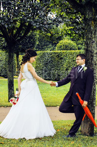 very beautiful bride with groom hugging and dancing in green park, lifestyle real people concept Stock photo © iordani