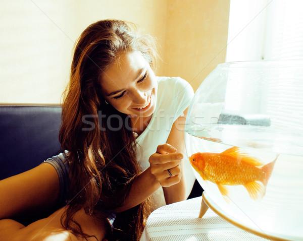 Güzel kadın gülen oynama akvaryum balığı ev güneş ışığı Stok fotoğraf © iordani