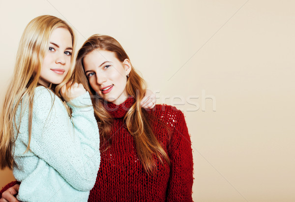 Two young girlfriends in winter sweaters indoors having fun. Lif Stock photo © iordani