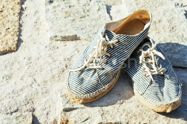 picture of vintage old shabby sneakers at seacost, real forgotte Stock photo © iordani