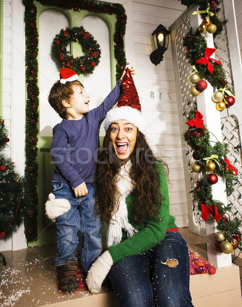 happy family on Christmas in red santas hats waiting gests and smiling infront of decorated house, m Stock photo © iordani