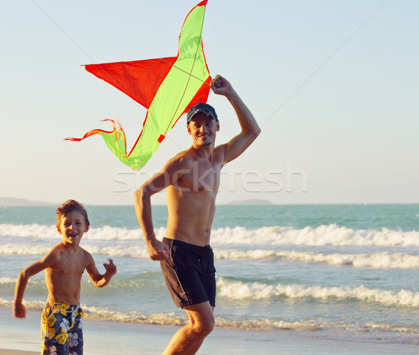 Stock photo: father with son, sunset at the seacoast playing kite, happy family