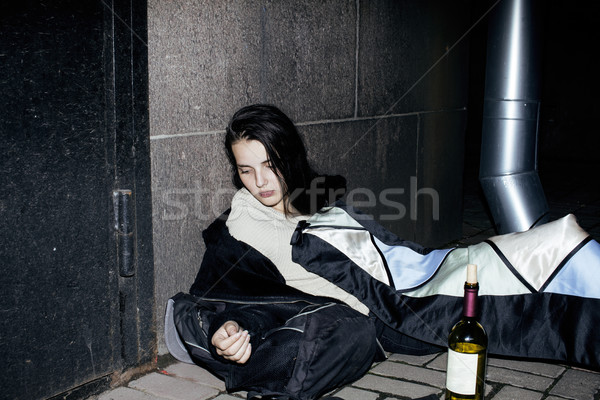young poor ttenage girl sitting at dirty wall on floor with bottle of vine, poor refugee alcoholic,  Stock photo © iordani