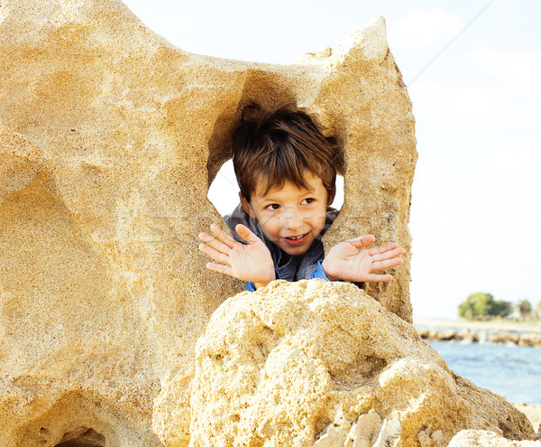 little cute boy on sea coast thumbs up playing with rocks Stock photo © iordani