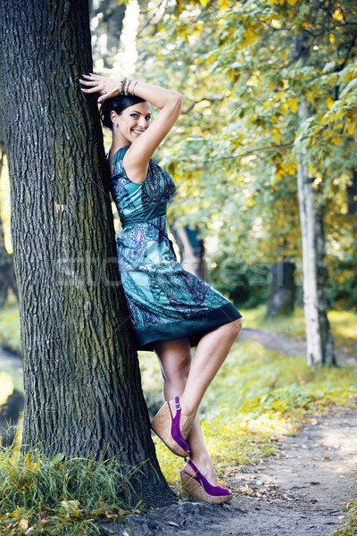 young pretty brunette woman in green park resting among grass an Stock photo © iordani