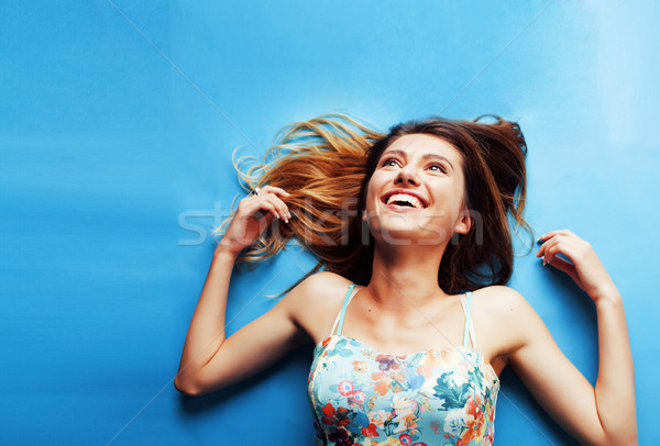young pretty woman fooling around on blue background Stock photo © iordani