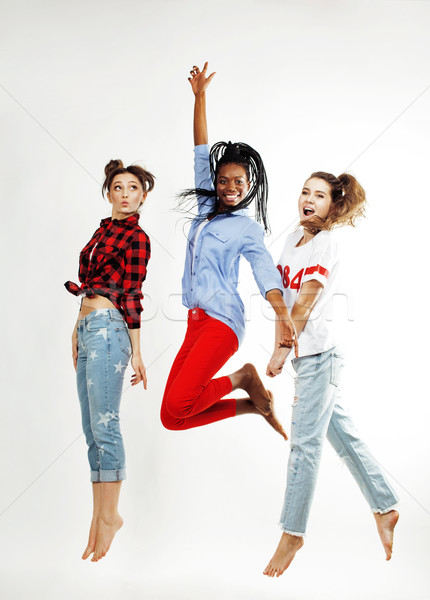 three pretty african american and caucasian, brunette and blonde teenage girl friends jumping happy  Stock photo © iordani