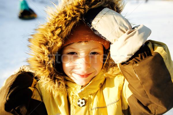 little cute boy in hood with fur on snow outside Stock photo © iordani