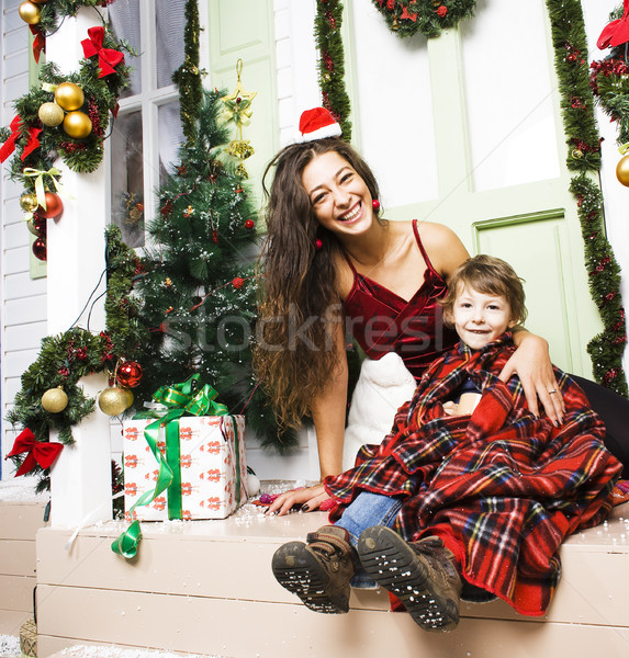 Stock photo: happy family on Christmas in red hats waiting gests and smiling
