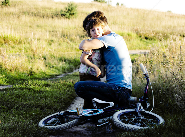 father learning his son to ride on bicycle outside, real happy f Stock photo © iordani