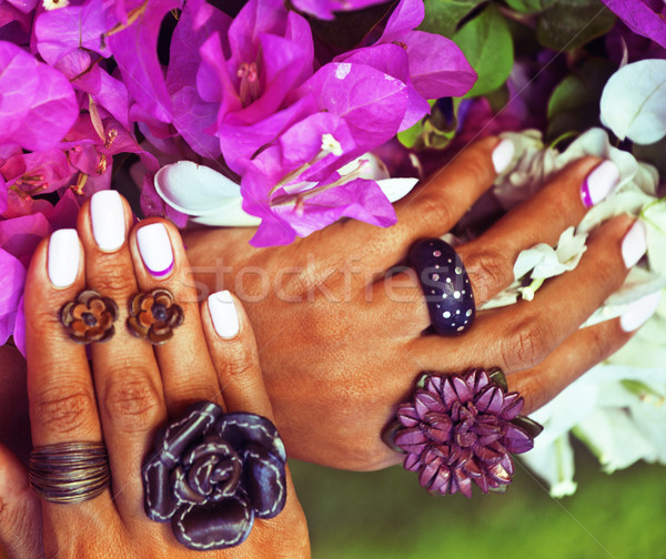 bright colorfull shot of african tanned hands with manicure among pink flowers wearing jewellery  Stock photo © iordani