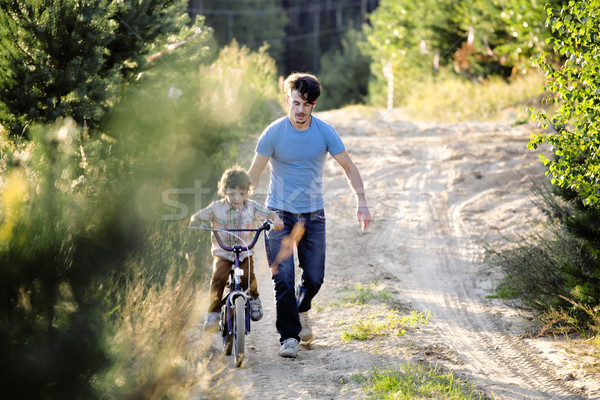 Stock photo: father learning his son to ride on bicycle outside, real happy family in summer forest enjoing natur