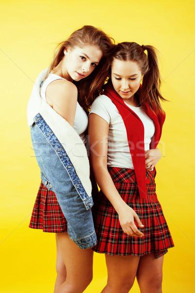 lifestyle people concept: two pretty young school teenage girls having fun happy smiling on yellow b Stock photo © iordani