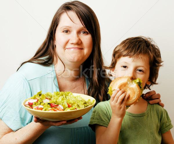 mature woman holding salad and little cute boy with hamburger te Stock photo © iordani