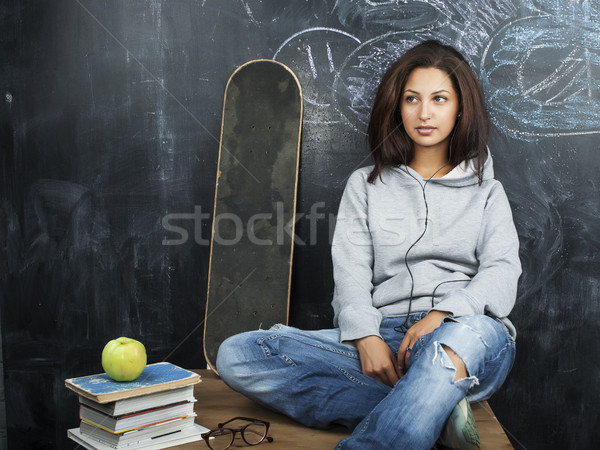 young cute teenage girl in classroom at blackboard seating on table smiling, modern hipster concept Stock photo © iordani