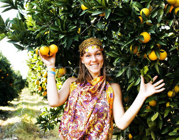 pretty woman in orange grove smiling Stock photo © iordani
