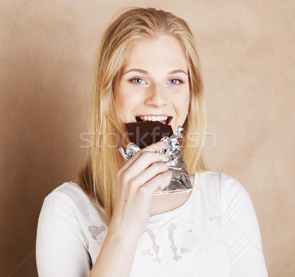 young beauty blond teenage girl eating chocolate smiling Stock photo © iordani