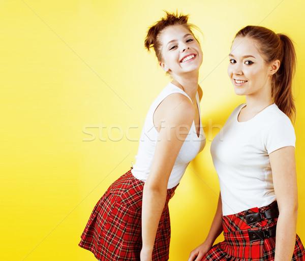 lifestyle people concept: two pretty school girl having fun on yellow background, happy smiling stud Stock photo © iordani