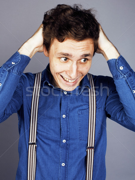 young goofy man with pimples pointing in studio Stock photo © iordani