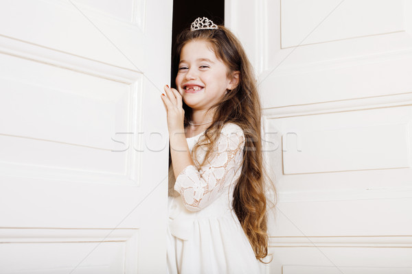 little cute girl at home, opening door well-dressed in white dress, adorable milk fairy teeth Stock photo © iordani