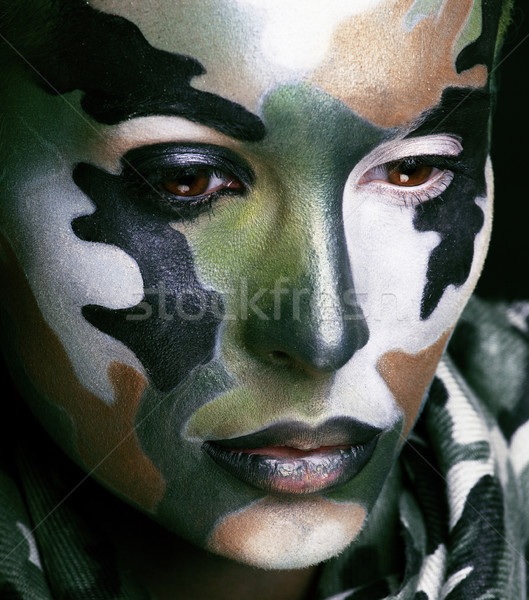 Beautiful young fashion woman with military style clothing and face paint make-up, khaki colored Stock photo © iordani