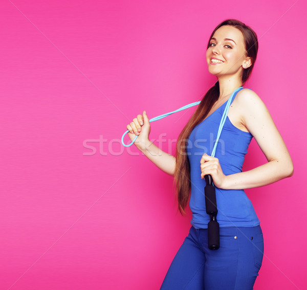 young happy slim girl with skipping rope on pink background Stock photo © iordani