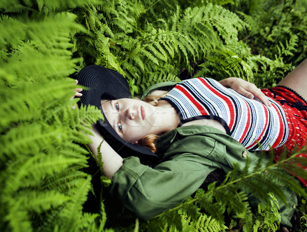 Pretty young blond girl hipster in hat among fern, vacation in green forest  Stock photo © iordani