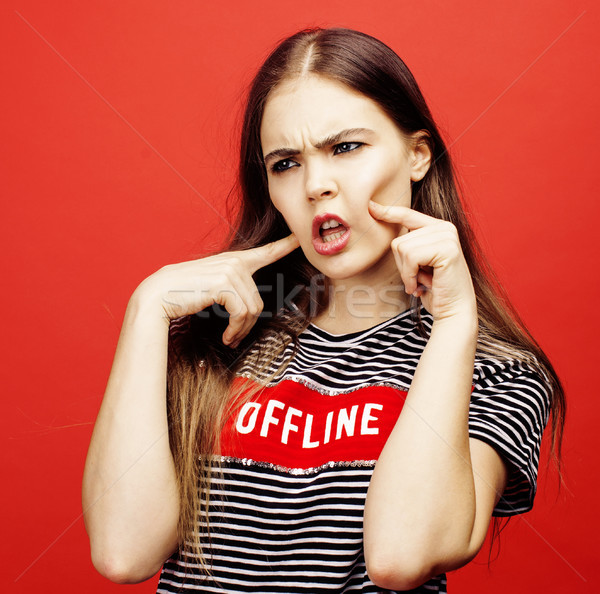 Stock photo: young pretty emitonal posing teenage girl on bright red background, happy smiling lifestyle people c