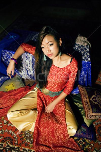 young pretty asian girl in bright colored interior on carpet Stock photo © iordani