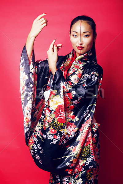 young pretty geisha on red background posing in kimono, oriental people concept close up Stock photo © iordani