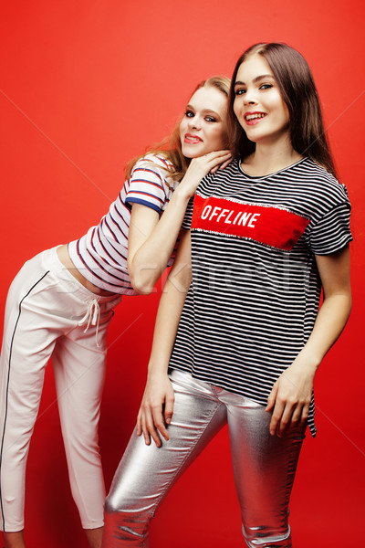 Stock photo: two best friends teenage girls together having fun, posing emotional on red background, besties happ