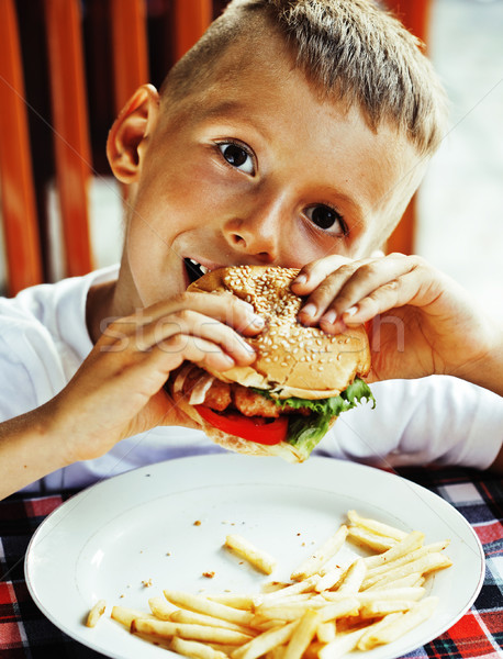 Stock photo: little cute boy 6 years old with hamburger and french fries maki