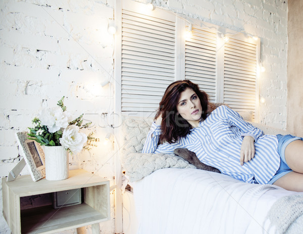 Stock photo: young pretty brunette woman in her bedroom sitting at window, happy smiling lifestyle people concept