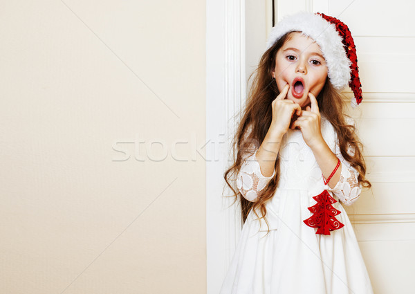 little cute girl in santas red hat waiting for Christmas gifts.  Stock photo © iordani