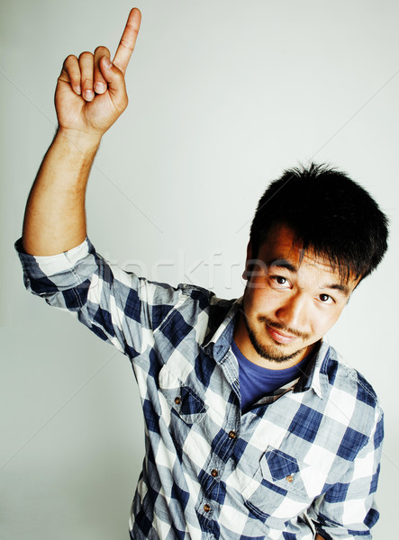 Stock photo: young cute asian man on white background gesturing emotional, pointing, smiling, lifestyle people co