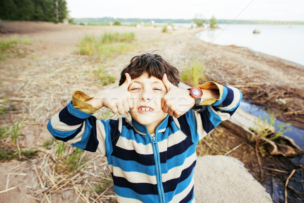 little cute boy smiling thumbs up on lake shore at summer vacati Stock photo © iordani