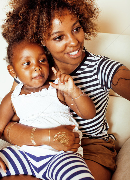 adorable sweet young afro-american mother with cute little daughter, hanging at home, having fun pla Stock photo © iordani