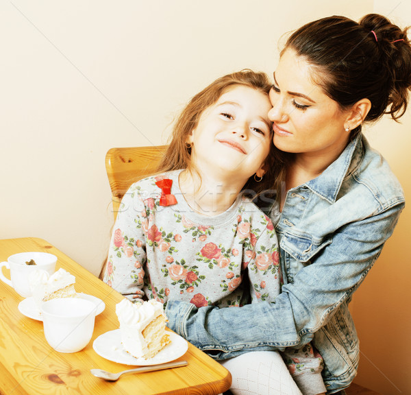 young mother with daughter on kitchen drinking tea together hugg Stock photo © iordani