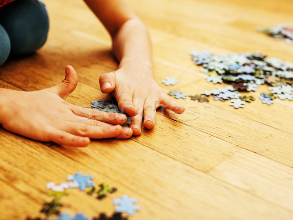 little kid playing with puzzles on wooden floor together with pa Stock photo © iordani