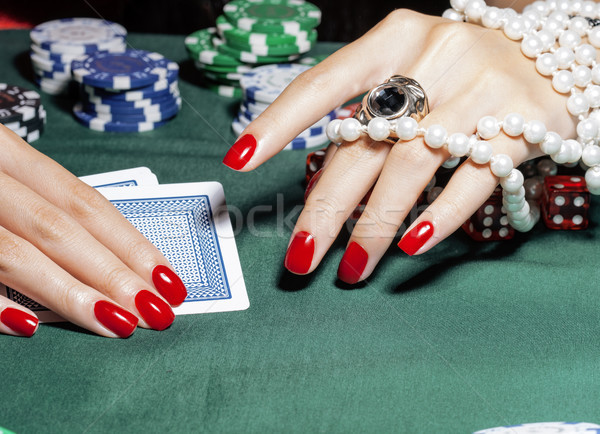 hands of young caucasian woman with red manicure at casino table Stock photo © iordani