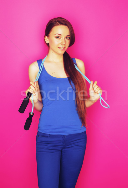 young pretty brunette girl posing emotional on pink background holding skipping rope , lifestyle spo Stock photo © iordani