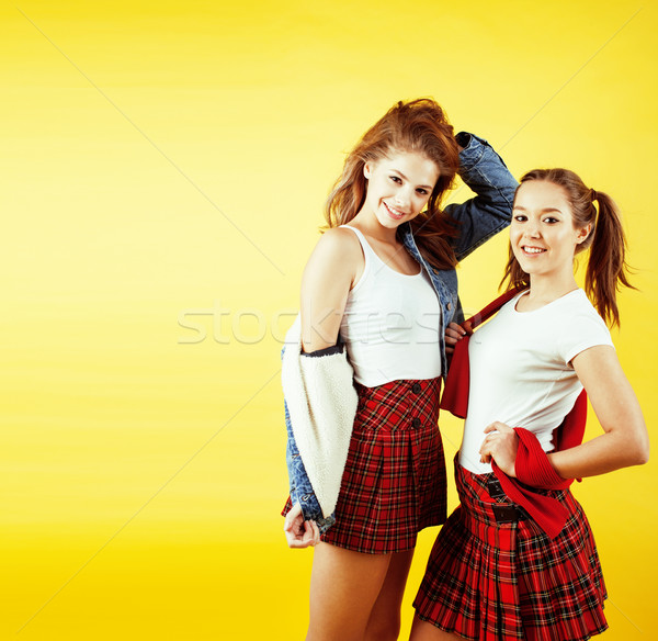 lifestyle people concept: two pretty school girl having fun on yellow background, happy smiling stud Stock photo © iordani