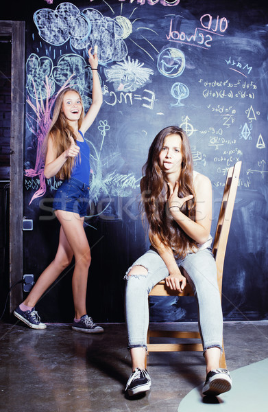 back to school after summer vacations, two teen girls in classroom with blackboard painted Stock photo © iordani